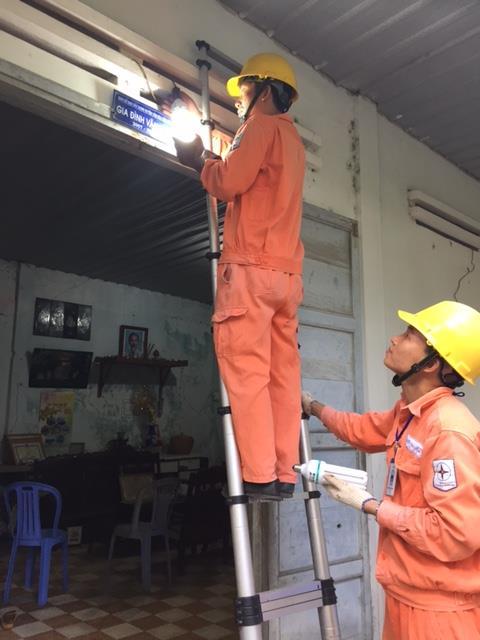 Công nhân Điện lực Côn Đảo thay bóng đèn tiết kiệm điện tại nhà dân. Ảnh: Mai Phương/BNEWS/TTXVN